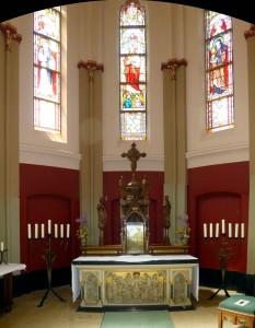 Het gerestaureerde priesterkoor met het houtgesneden altaar, waarvan het retabel is verwijderd