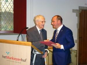 wethouder Arjan van der Weegen biedt Herman Huismans het eerste boek aan