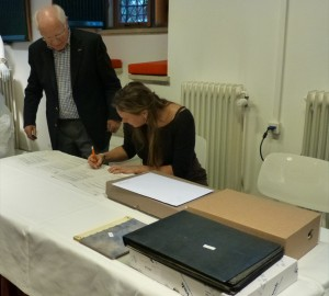 Mireille Franken tekent namens Markiezenhof voor ontvangst. Op de voorgrond is een deel van het archief zichtbaar, inclusief het handgeschreven 'dagboek'' van Hubertus Beckers