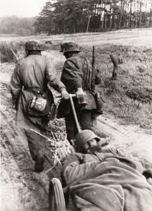 Twee Duitse militairen zijn van onder Woensdrecht met een gewonde maat op weg naar het lazaret op Vrederust