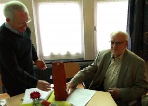 Wim van Nieuwenhuijzen neemt met zichtbaar genoegen de kleine blijk van waardering in ontvangst