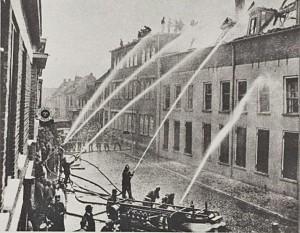 De Brandweer actief met blussen. Op de achtergrond het zgn Fraba-gebouw
