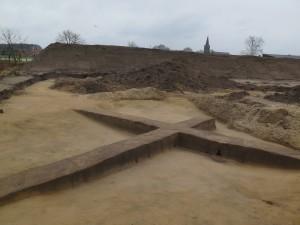 Opgraving in Nispen toont de wijze waarop het terrein zorgvuldig wordt afgeschaafd. In de zijwanden van het kruis zijn paalsporen te zien. Klik voor een vergroting op de afbeelding.
