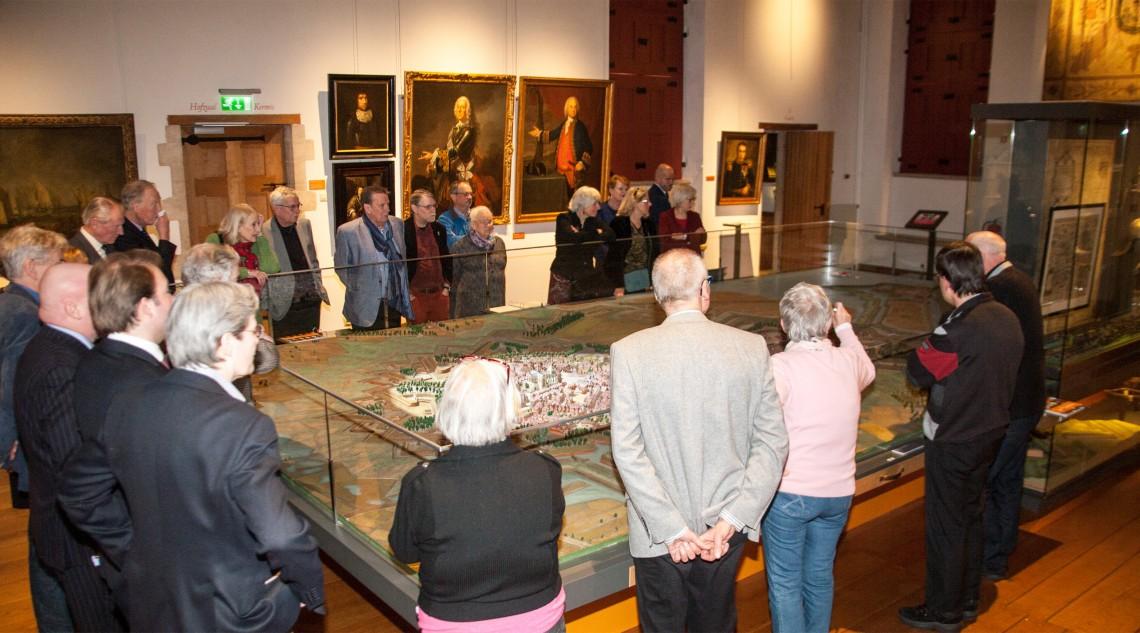De nazaten van Carleton en Van Gorkum krijgen een toelichting op de aanval bij de maquette van Henk van Tilborg. Op de achtergrond kijkt J.E van Gorkum goedkeurend toe (links naast de deur).