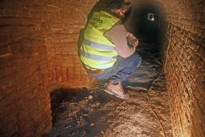 De miniersgang is alleen gehurkt of kruipend toegankelijk. Links is een van de luister-nissen te zien. Het verlichte eind van de gang ligt aan de andere kant van de Zuidoostsingel