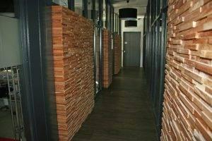 De toegang naar de kantoren op de eerste verdieping. De wandjes zijn opgebouwd met houten stripjes