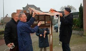 Het bord wordt met vereende krachten onthuld: Wethouder van de Velden, bewoner Van Loon, werkgroepleden Ria Weyts (achter bord) en Eric Goossen